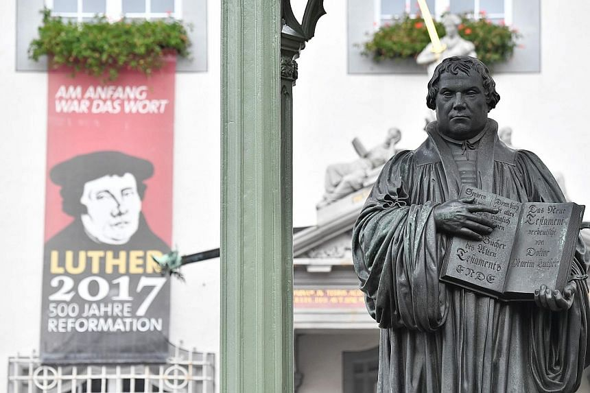 A statue of theologian Martin Luther in Wittenberg. German Chancellor Angela Merkel and President Frank-Walter Steinmeier yesterday attended a service at the church where Luther is said to have first displayed his list of criticisms of the Catholic C