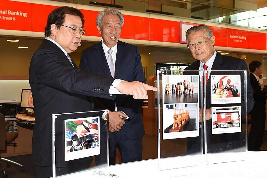 Deputy Prime Minister Teo Chee Hean (centre) viewing one of the displays at the public exhibition on Wind Behind The Sails: The Story Of The People And Ethos Of OCBC with OCBC Bank chairman Ooi Sang Kuang (right) and OCBC Bank Group CEO Samuel Tsien.