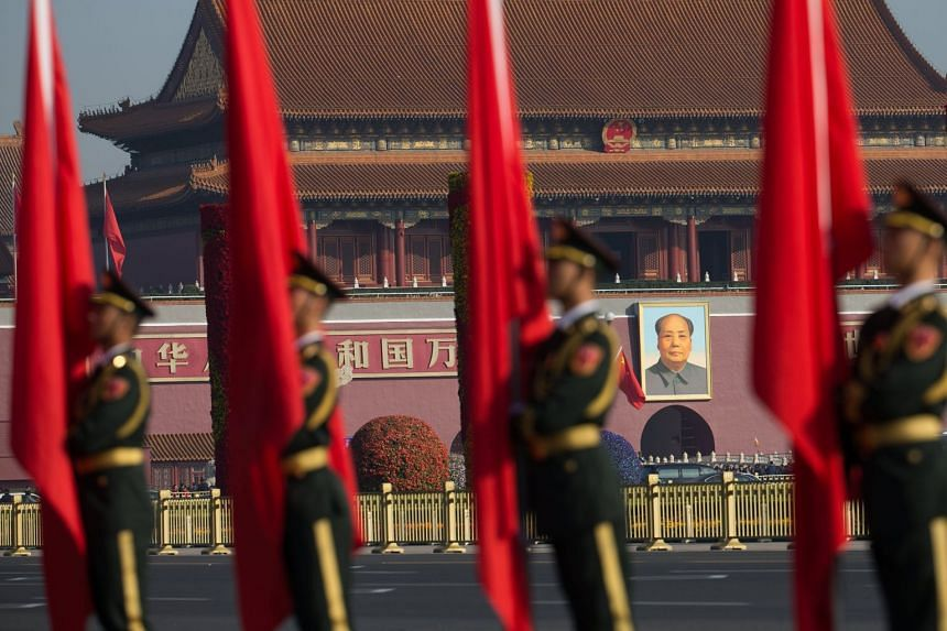Soldiers of the Chinese People's Liberation Army honor guard stand in front of a portrait of Chairman Mao on the south gate of the Forbidden City.