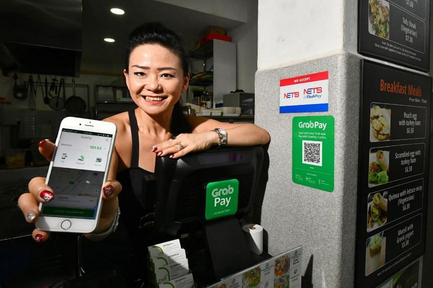 Ms Gloria Soo, 45, Founder of EnerGi Food, showing the Grab screen for customers to pay for her food via GrabPay at her stall at Eden Garden Cafe on Nov 1, 2017.