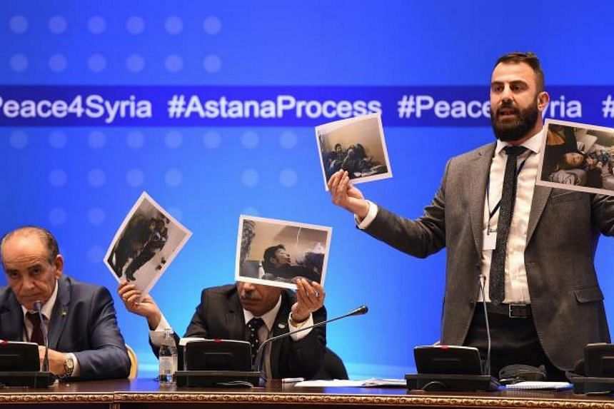 Member of Syrian armed opposition Yasir Abdur Rakhim (right) speaks as he demonstrates photo documents, during a press conference after the seventh round of talks on the Syrian conflict settlement in Astana, Kazakhstan on Oct 31, 2017.