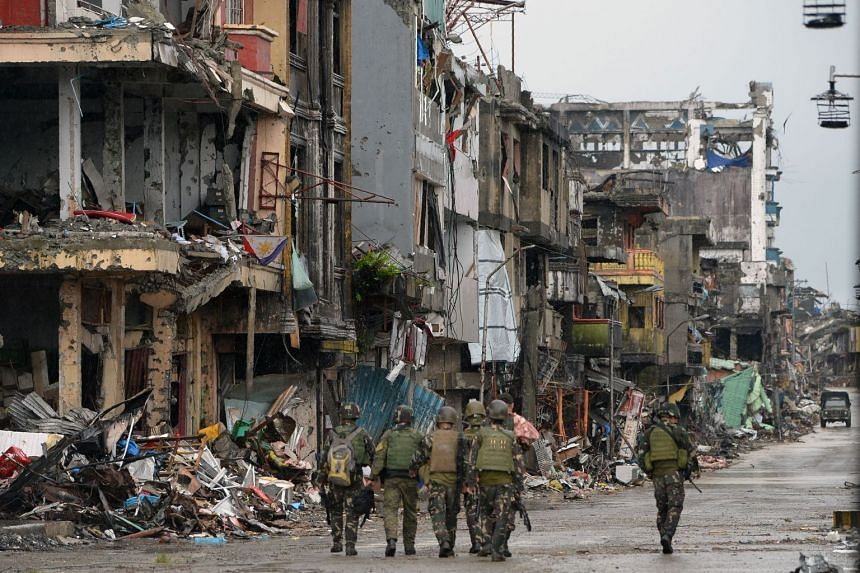 Philippine soldiers walking past battle-scarred buildings in Marawi on Oct 17, 2017.