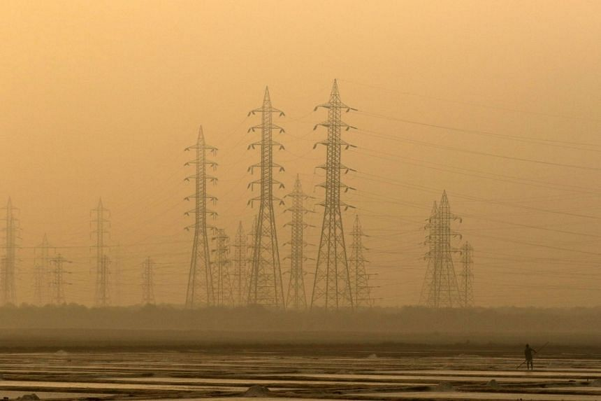 A worker levels a salt pan near electricity pylons in Mumbai, India, on Jan 16, 2017.