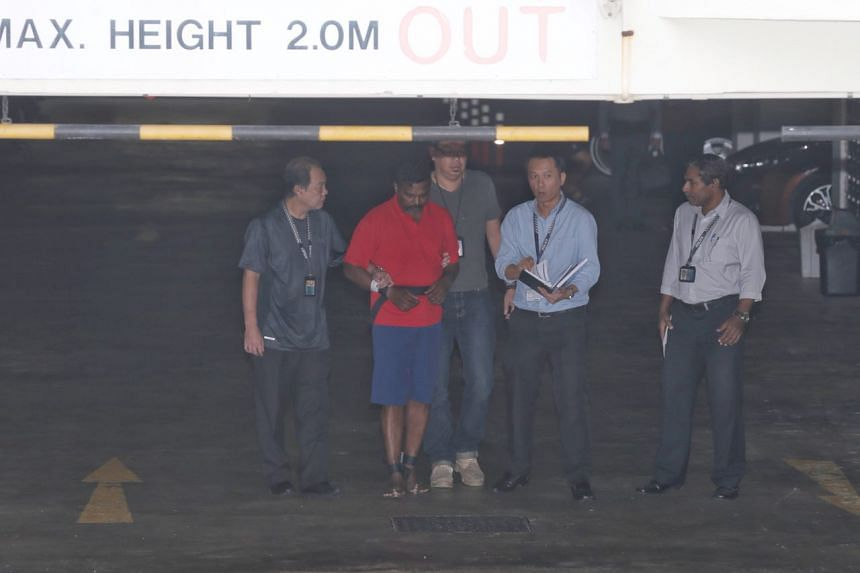 Krishnan Raju and several officers at the basement carpark of the condo, before he was brought to the unit where the crime took place.