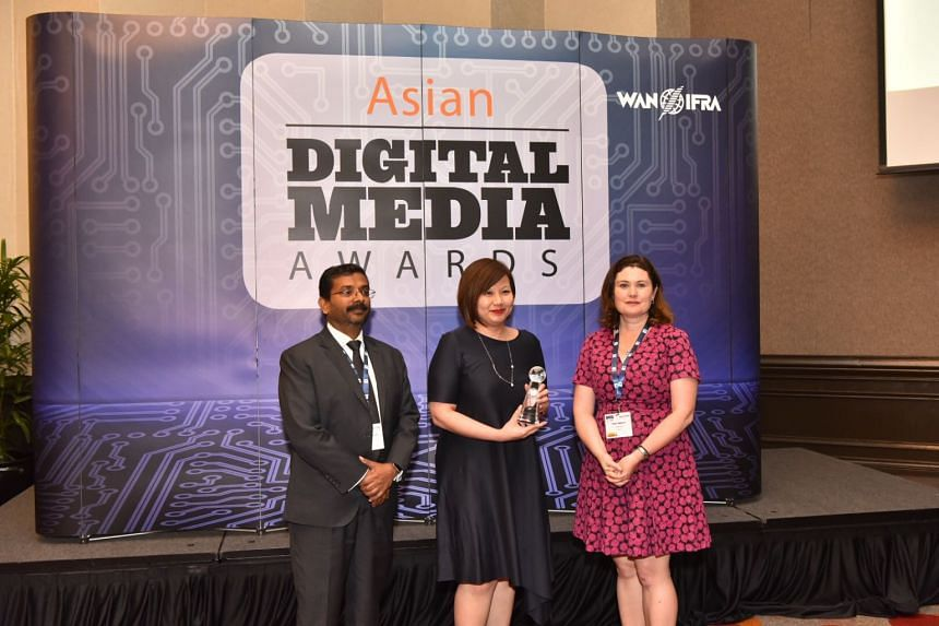 ST digital editor Ong Hwee Hwee (centre) accepting the award for an online feature on Joseph Schooling's Road to Rio, at the Asian Digital Media Awards on Nov 1, 2017.