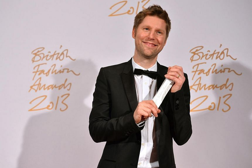 Christopher Bailey, Chief Creative Officer of Burberry, poses with the trophy for Menswear Designer of the Year at the British Fashion Awards in London.