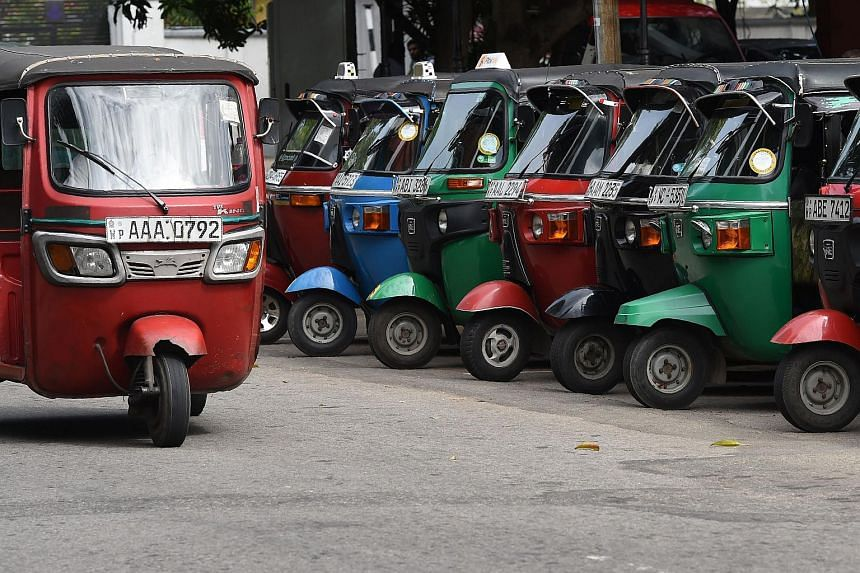 An autorickshaw driving past a row of the parked three-wheel taxis on a road in Colombo. There are 1.2 million auto drivers in Sri Lanka - far more than is needed for a small island of 21 million.