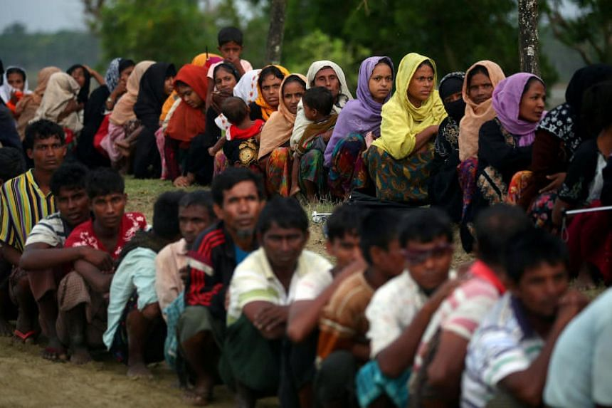 Rohingya refugees wait to receive permission from the Bangladeshi army to continue their way after crossing the Bangladesh-Myanmar border, at a port in Teknaf, Bangladesh on Oct 31, 2017.