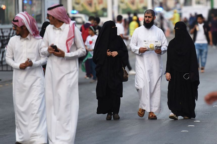 People walk on Tahlia street in the Saudi capital Riyadh on Sept 24, 2017, during celebrations for the anniversary of the founding of the kingdom.