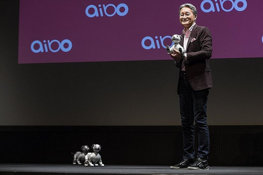 Sony chief executive officer Kazuo Hirai holding one of the company's new robotic dogs. The AI-enabled canine comes with new sensing and movement technologies as well as far more advanced AI backed by cloud computing to develop the dog's personality.