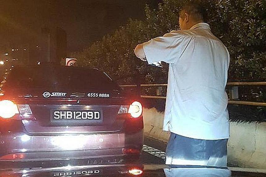 The cabby (above) taking photos of his vehicle during the incident. Mr Chia Hock Herng, the Audi driver accused of rear-ending the taxi, said the cabby got out of his vehicle and appeared to want to help, but later claimed his taxi was hit.