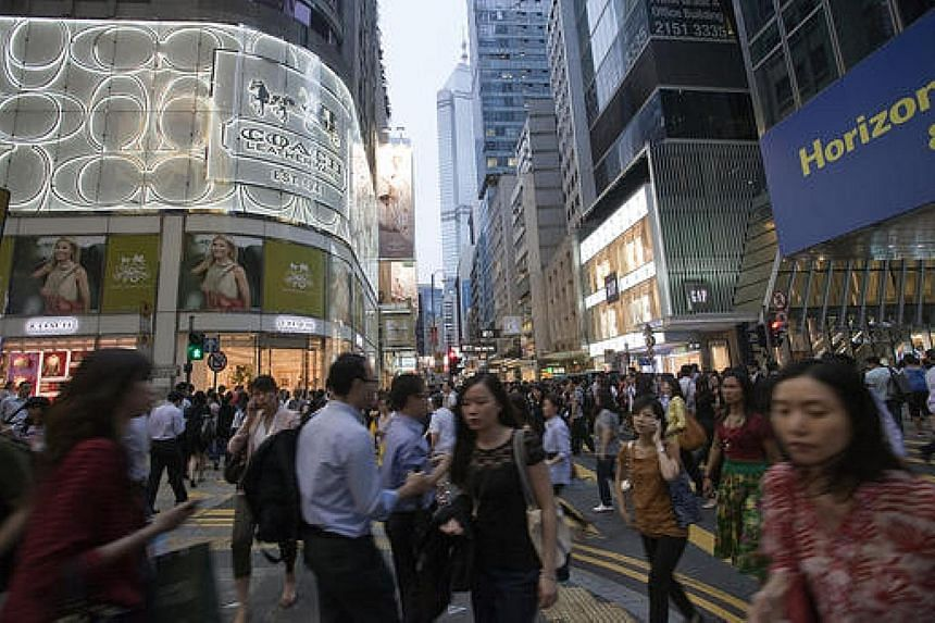A Coach store (left) on Queen's Road in Hong Kong. Both Coach and Glencore cited weak demand for their shares as the reason to delist.