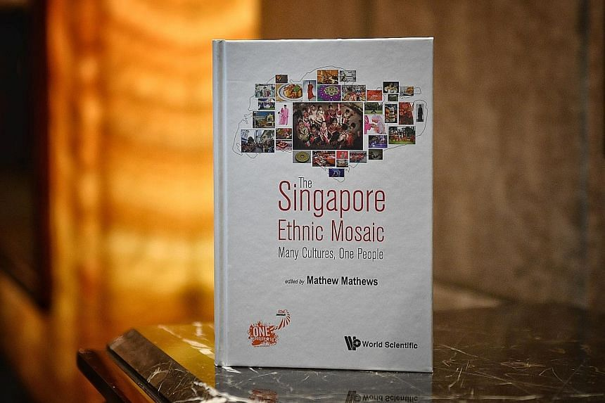 Prime Minister Lee Hsien Loong chatting with facilitators and mentors from OnePeople.sg at its 10th anniversary dinner last night. He also launched a commemorative book (above) featuring various sub-ethnic groups in Singapore.