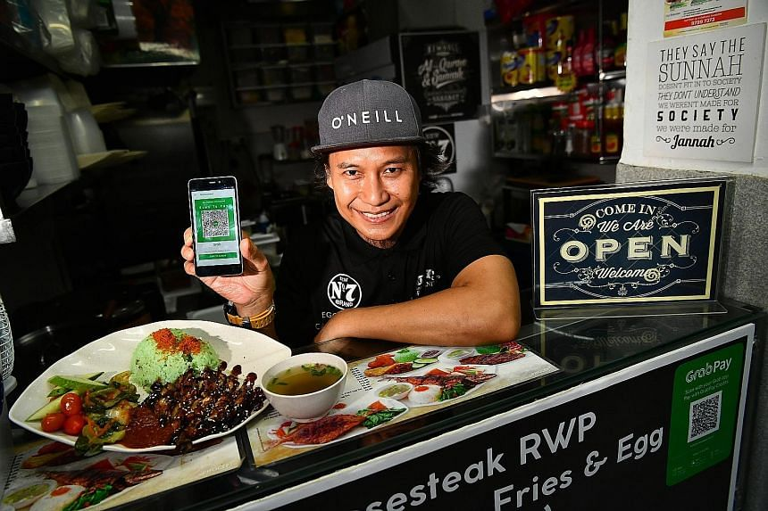 Mr Nornizam Amin, 46, owner of Rayyan's Waroeng Penyet, with his signature ayam penyet dish and the QR code for his stall at Eden Garden Cafe in Telok Ayer Street yesterday, His is one of 25 restaurants and hawker stalls accepting GrabPay.