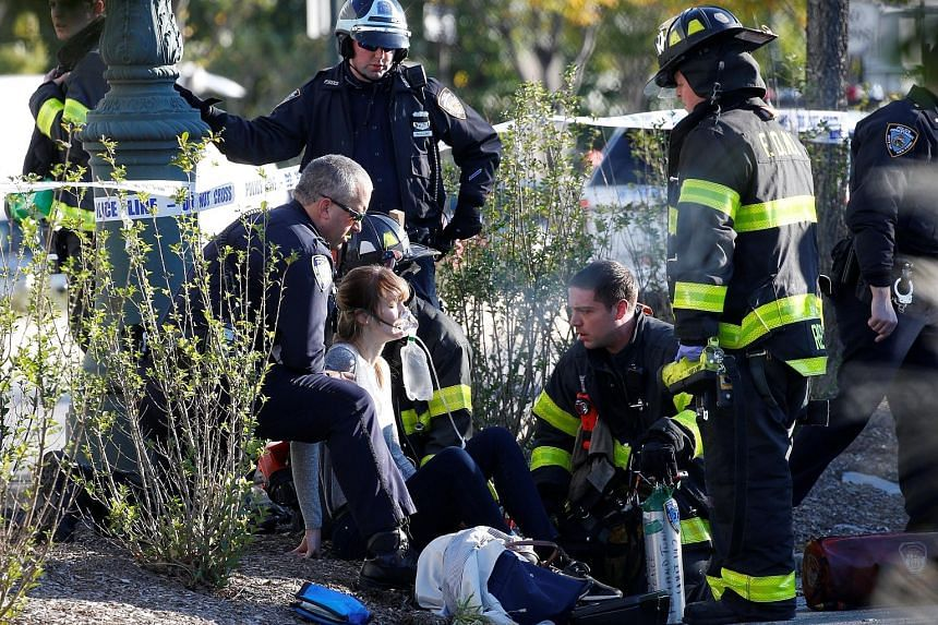 Above: The scene of the attack, in which a man drove onto a bicycle path in New York on Tuesday, mowing down anyone in his path. Below: Emergency personnel giving first aid to a woman who was injured during the attack.