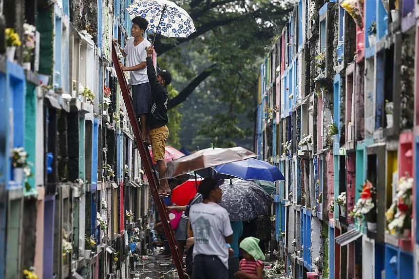Filipinos placing candles at the grave sites of departed loved ones at a public cemetery in Quezon City, east of Manila, yesterday. Catholics in the Philippines follow tradition and flock to cemeteries to remember departed relatives and loved ones on