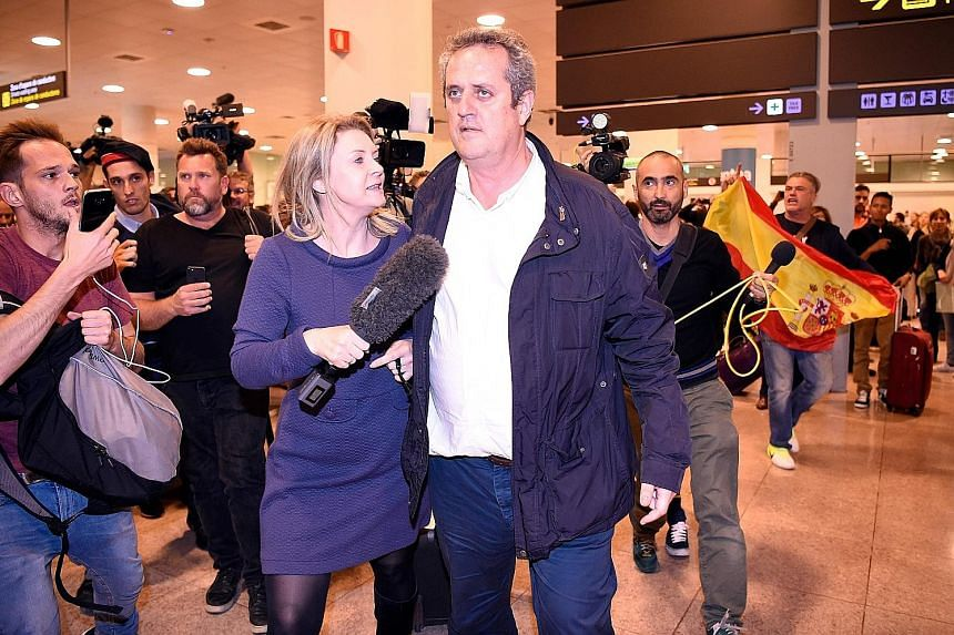 Catalonia's former interior chief, Mr Joaquim Forn, being followed by journalists as a man with a Spanish flag shouts at him upon his arrival at El Prat airport in Barcelona after flying from Brussels on Tuesday.