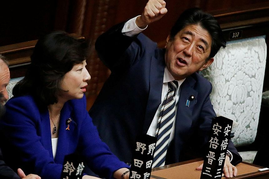 Prime Minister Shinzo Abe gesturing as he talks to Liberal Democratic Party lawmaker Seiko Noda at the Lower House in Tokyo yesterday.
