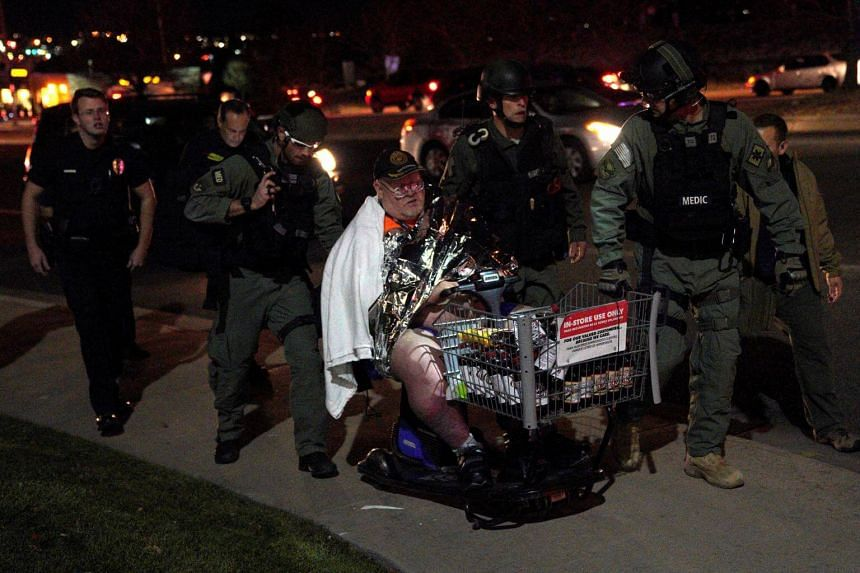 A man is evacuated in a Walmart cart by SWAT medics from the scene.