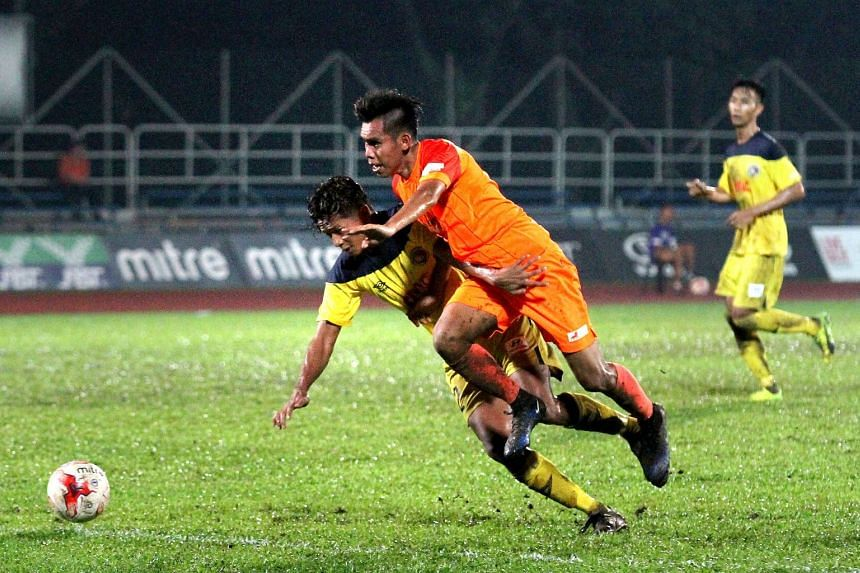 Hougang United midfielder Azhar Sairudin (in orange) challenging for the ball with a Balestier Khalsa opponent during their Great Eastern-Hyundai S.League match at Hougang Stadium on April 27, 2017.