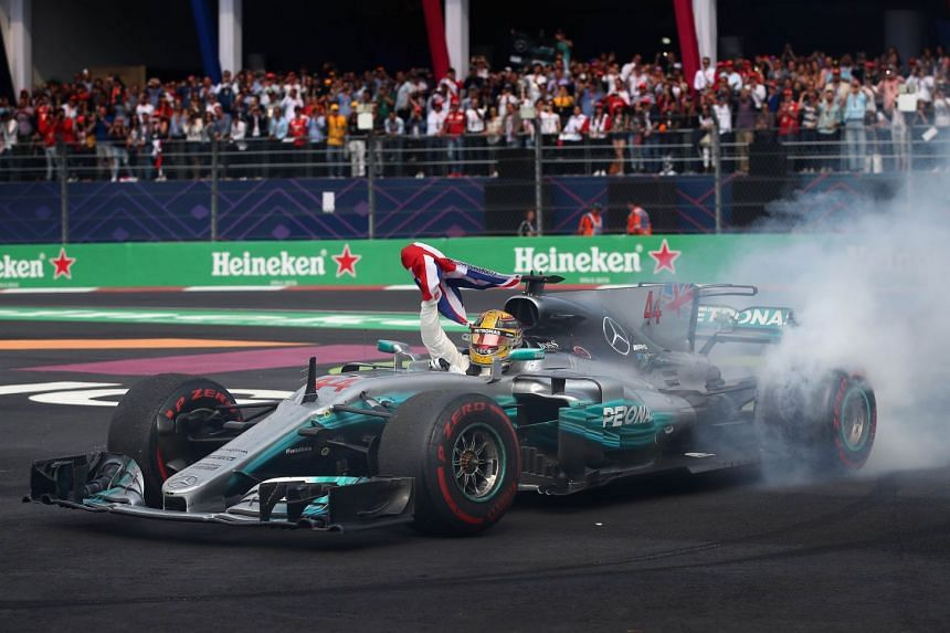 Lewis Hamilton celebrates in his Mercedes after winning his fourth F1 World Drivers Championship.