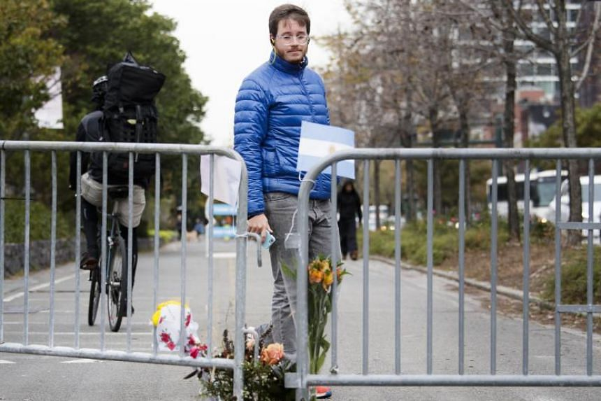 A man looks at a makeshift memorial which includes Argentinian and Belgian flags at the scene of the New York attack.