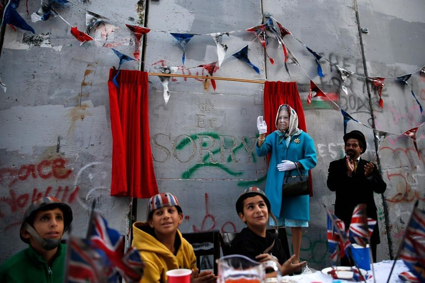 An actor dressed up as Queen Elizabeth and Palestinian children from the al-Aida refugee camp attend an event held by secretive British street artist Banksy on Nov 1, 2017.