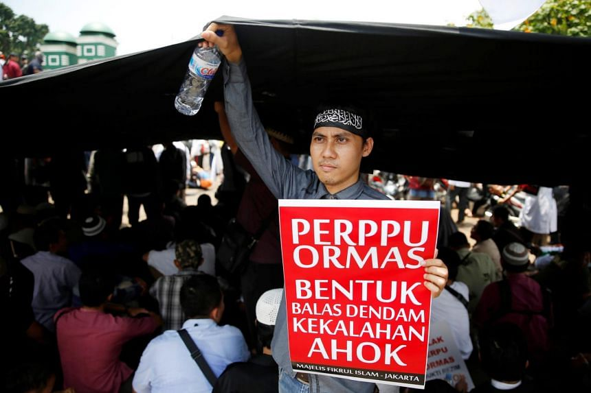 An Indonesian Islamist group member holds a placard during a protest against President Joko Widodo's decree to disband certain groups, in front of the parliament building in Jakarta, Indonesia, on Oct 24, 2017.