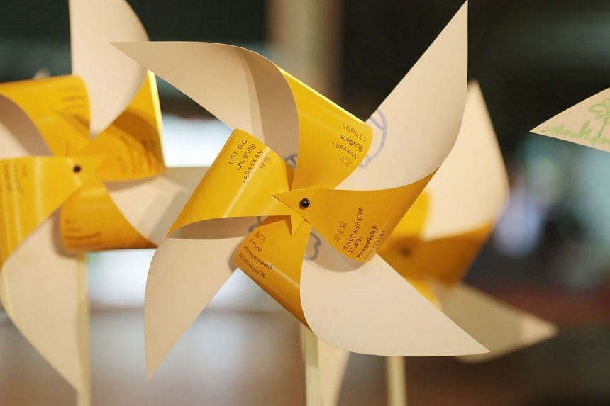 Pinwheels bearing messages from participants at the arts event. People were asked to write down what would make it easier for them to accept death. Volunteer Angeline Cheong in a discussion with some people in the audience. She said death can be a le