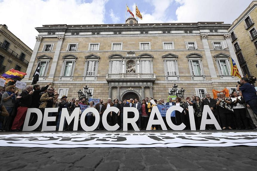 "Protesters standing behind a ""Democracy"" sign in Barcelona yesterday as members of the deposed Catalan government were being questioned in Madrid."