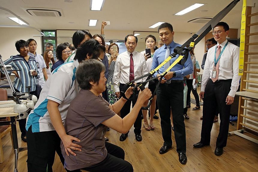 (From right) NTUC Health's residential care head Leon Luai, Speaker of Parliament Tan Chuan-Jin and NTUC Health chief executive Chua Song Khim observing former nursing home resident Ang Cheh Eng doing exercises, at the official opening of NTUC Health