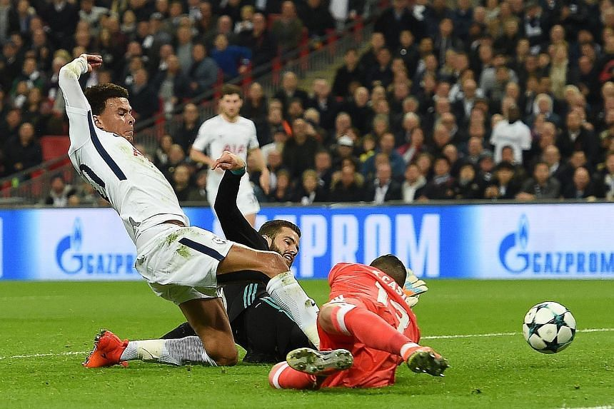 Top: Tottenham's Dele Alli getting to the ball first for Tottenham to open accounts against Real Madrid in their Champions League match at Wembley on Wednesday night. Above: The expressions on the faces of Real's Toni Kroos and Cristiano Ronaldo duri