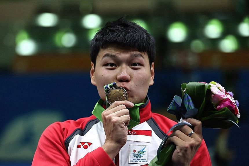 """Lim Wei Wen kissing his historic bronze medal at the Incheon Asian Games in 2014. Hampered by tennis elbow, he says he will """"take a step back, slow down and see what I really want""""."""