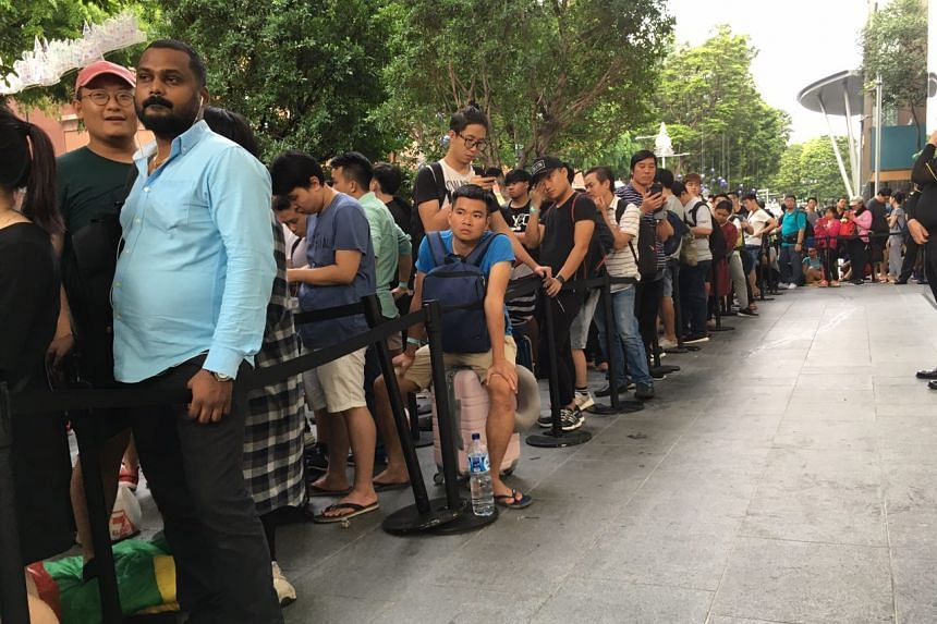 Customers wait in line to purchase the new iPhone X outside the Apple store in Orchard Road.