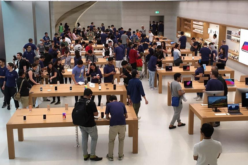 Customers get their hands on the new iPhone X at the Apple store in Orchard Road.