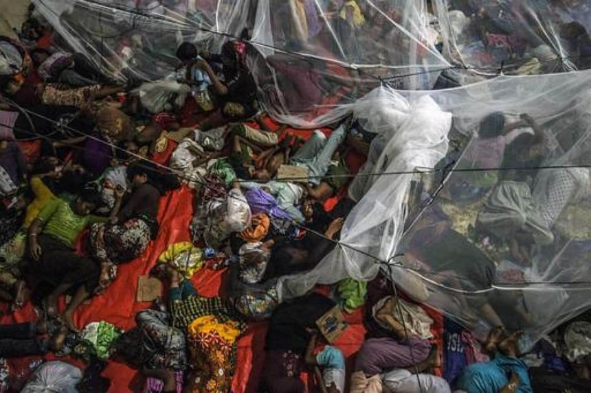 Rohingya migrants sleep together at the new confinement area in the fishing town of Kuala Langsa in Aceh province.