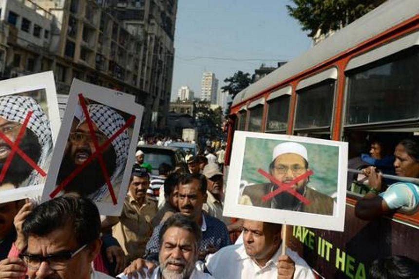 An Indian bus passenger watches as activists carry photographs of the chief of Jaish-e-Mohammad, Maulana Masood Azhar (left).