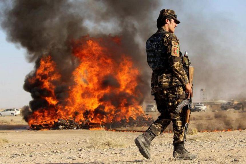 An Afghan soldier stands guard as authorities burn drugs in Helmand, Afghanistan, on Nov 2, 2017.