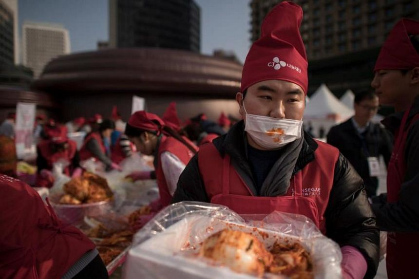 A man carries a box of kimchi during an annual kimchi-making festival in central Seoul on Nov 3, 2017.