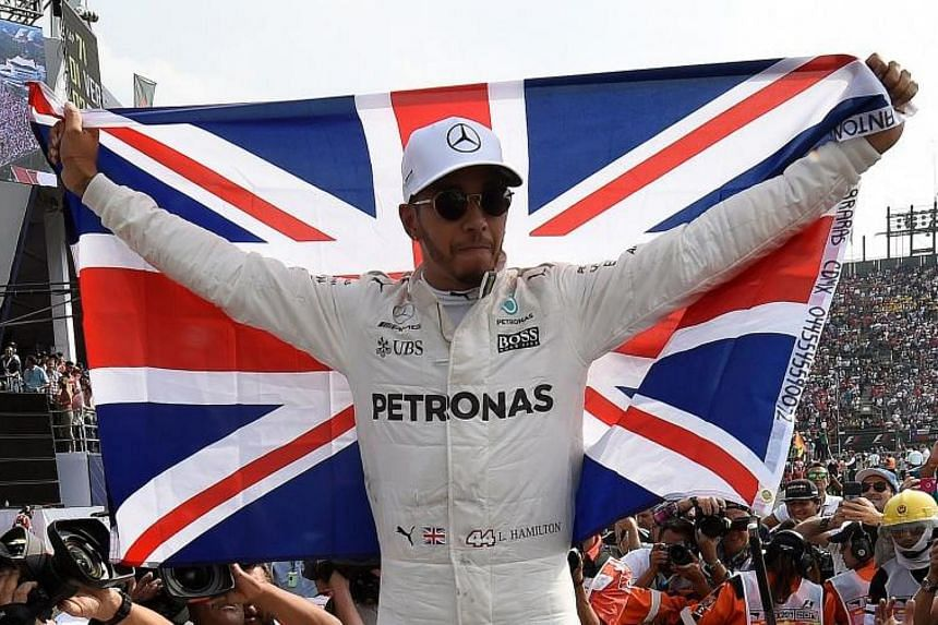 Mercedes' British driver Lewis Hamilton celebrates after winning his fourth Formula One world title at the Hermanos Rodriguez circuit in Mexico City on Oct 29, 2017.