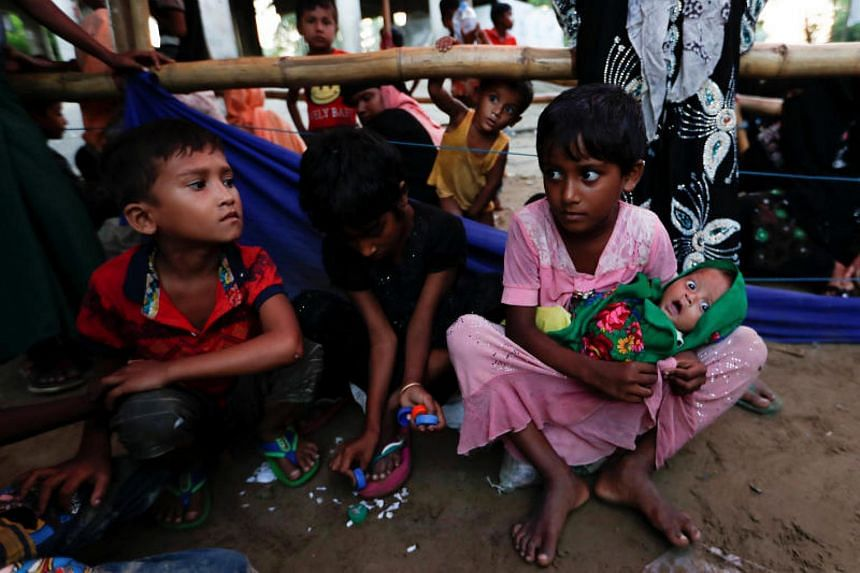 Rohingya refugee children sit as they wait for permission from the Bangladeshi army to continue at a registration center in Teknaf, Bangladesh, on Oct 15, 2017.