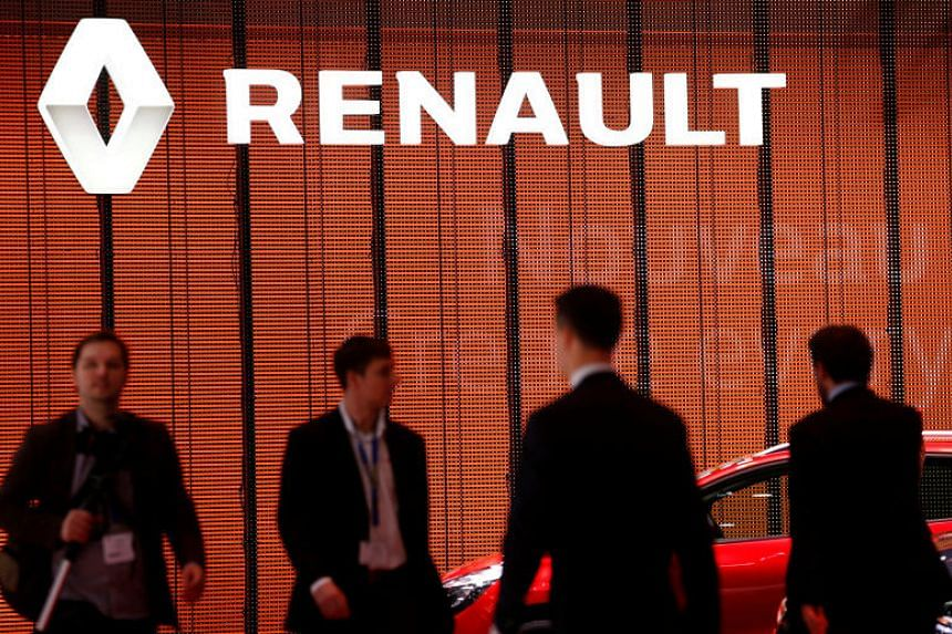 Visitors walk past a Renault logo on the car maker's booth during the second media day of the 86th International Motor Show in Geneva, Switzerland, on March 2, 2016.