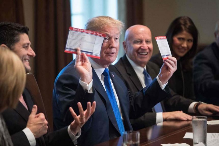 US President Donald Trump shows samples of the proposed new tax form as he meets with House Republican leaders and Republican members of the House Ways and Means Committee at the White House in Washington, DC, on Nov 2, 2017.