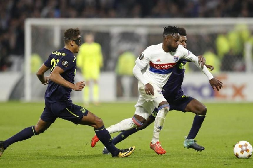 Maxwell Cornet (centre) of Olympique Lyon in action against Beni Baningime (right) and Dominic Calvert-Lewin (left) of Everton FC during the UEFA Europa League soccer match between Olympique Lyon and Everton FC in Decines-Charpieu, near Lyon, France,