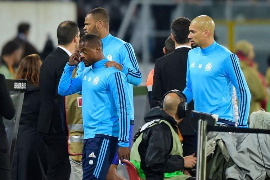 Marseille's French defender Patrice Evra (front) is escorted off the pitch by team-mates Portuguese defender Rolando and Brazilian defender Doria (right) after an argument with supporters before the start of the Europa League match against Vitoria SC