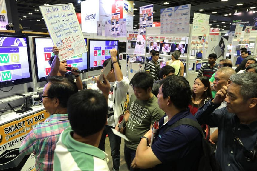 Visitors to the consumer electronics fair at Suntec Convention and Exhibition Centre looking at products on Friday, Nov 3, 2017 .