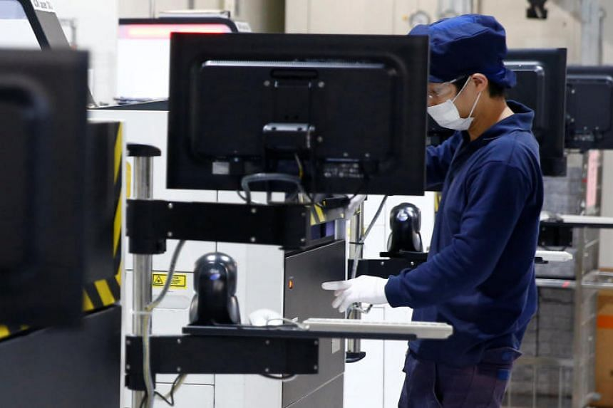An employees works at a production line during a tour of an REC solar panel manufacturing plant in Singapore.
