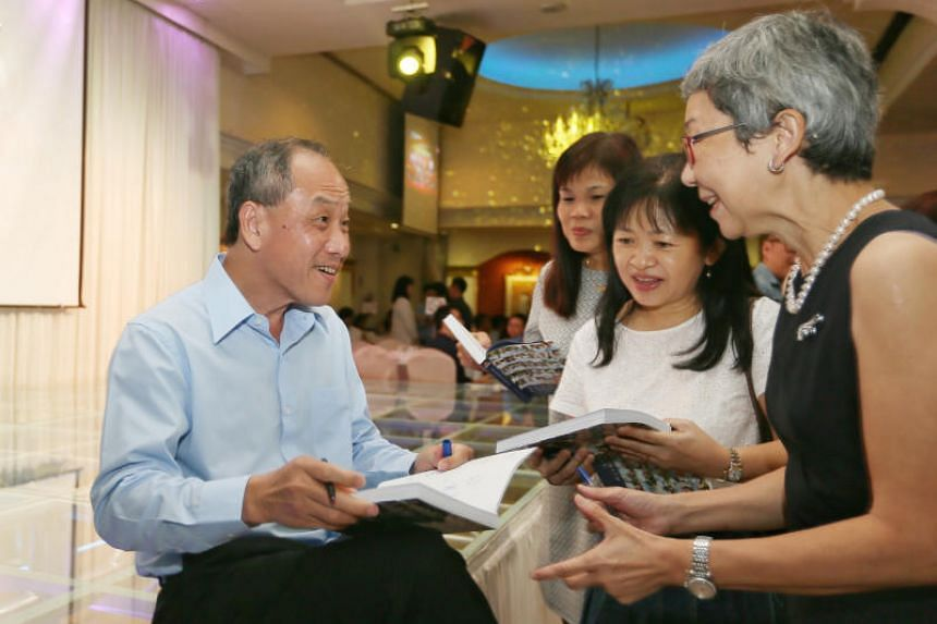 Workers' Party chief Low Thia Khiang signing autographs at the party's 60th anniversary celebration on Nov 3, 2017.