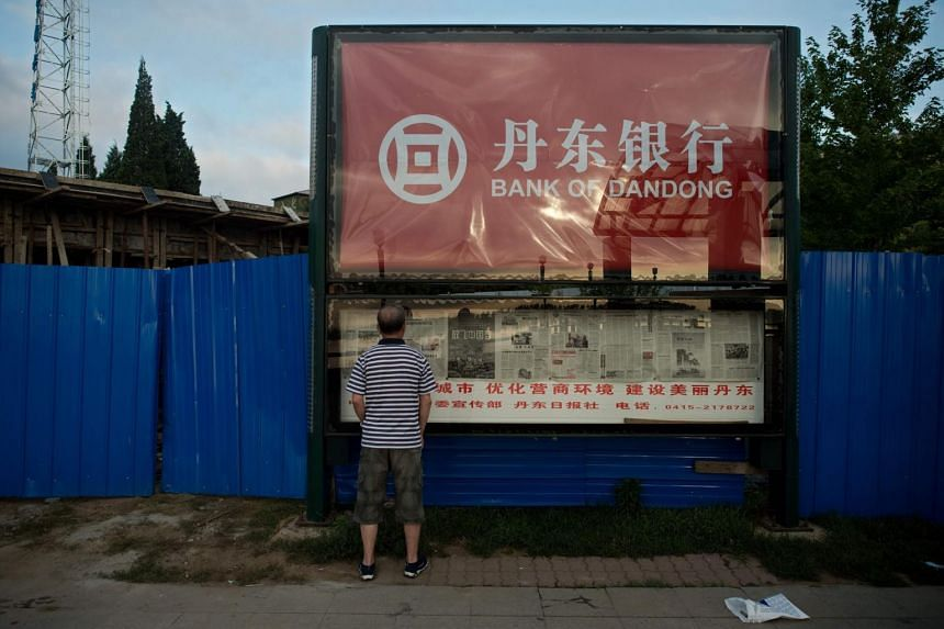 A man reads a newspaper displayed in a window billboard featuring a commercial for the Bank of Dandong.