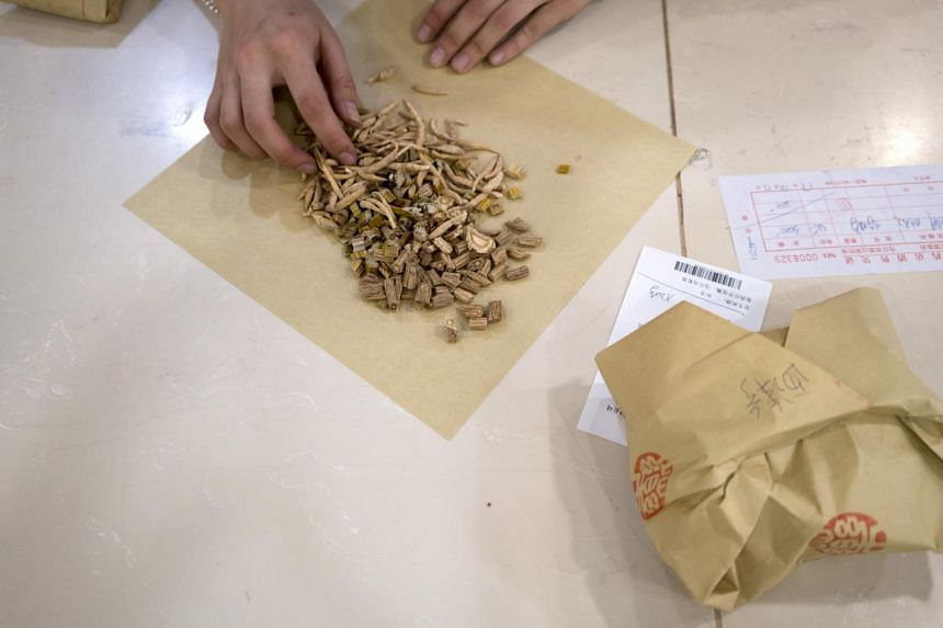 An employee prepares a packet of ingredients at a traditional Chinese medicine pharmacy in Beijing.